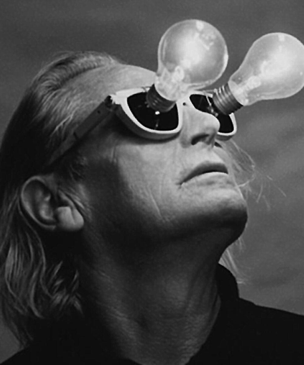 Primo piano di Ingo Maurer con degli occhiali con i bulbi della lampadina